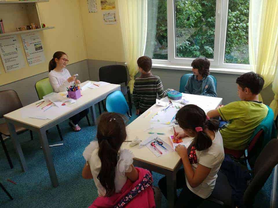Деца пишат непознати думи на цветни листчета в сугестопедичен курс по английски