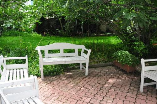 Тайната градина в KREG с три бели пейки, зелена трева и дървета.