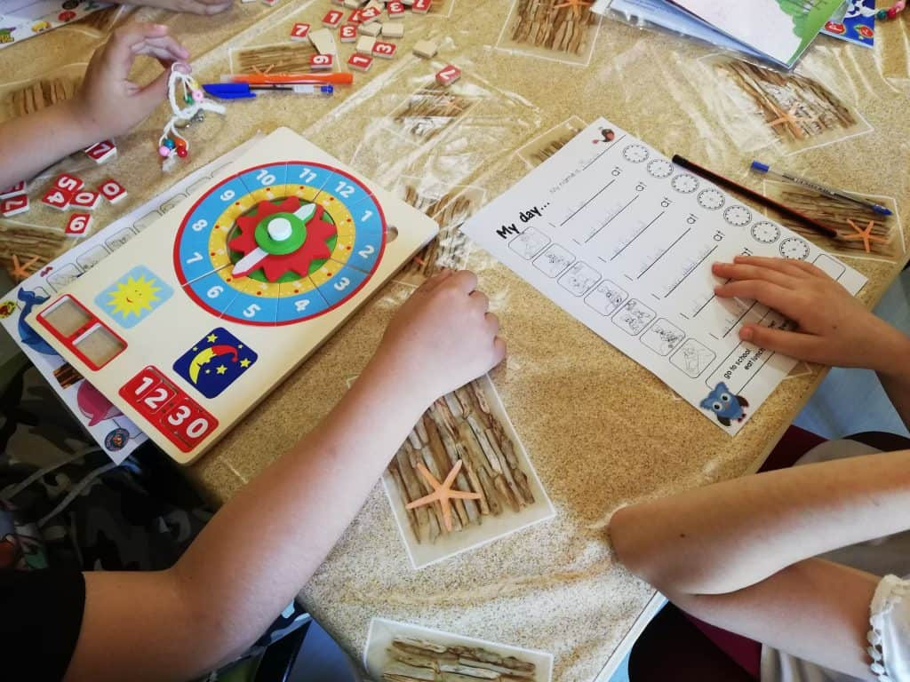 """Ръце на деца върху маса с учебен часовник и упражнение за писане на тема """"Моят ден по часове"""""""