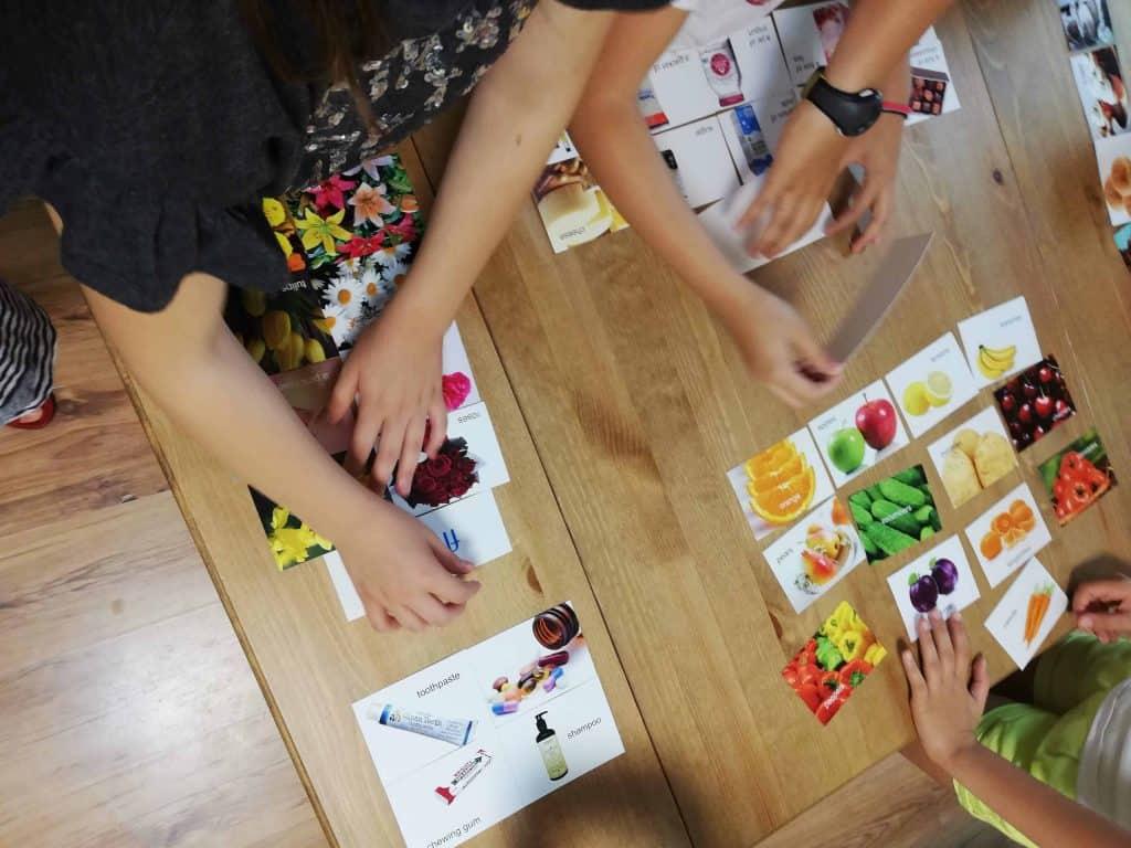 Ръце на деца, които подреждат карти с думи и картинки в сугестопедична игра