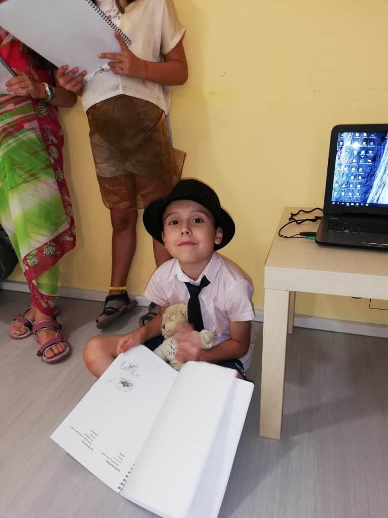 Дете с бомбе и вратовръзка седи на пода с книга в ръка и се усмихва на камерата