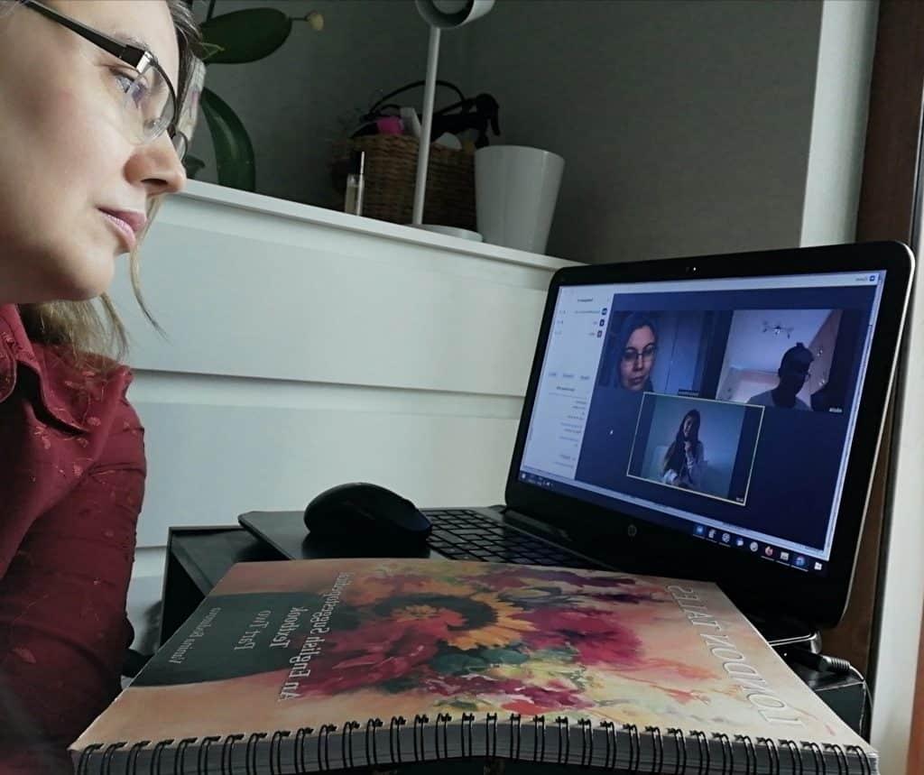 Жена с очила в профил гледа екран, на който тече сугестопедичен курс онлайн