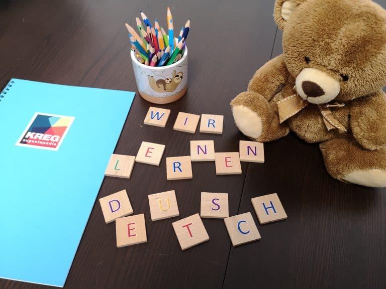 Шарени букви образуващи надпис Wir lernen Deutsch, синя тетрадка, шарени моливи и мече за сугестопедичния курс по немски за деца в KREG
